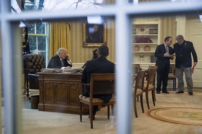 Presidente dos EUA, Donald Trump, conversa por telefone com a primeira-ministra da Alemanha, Angela Merkel, na Sala Oval da Casa Branca, Washington, 28 de janeiro de 2017.