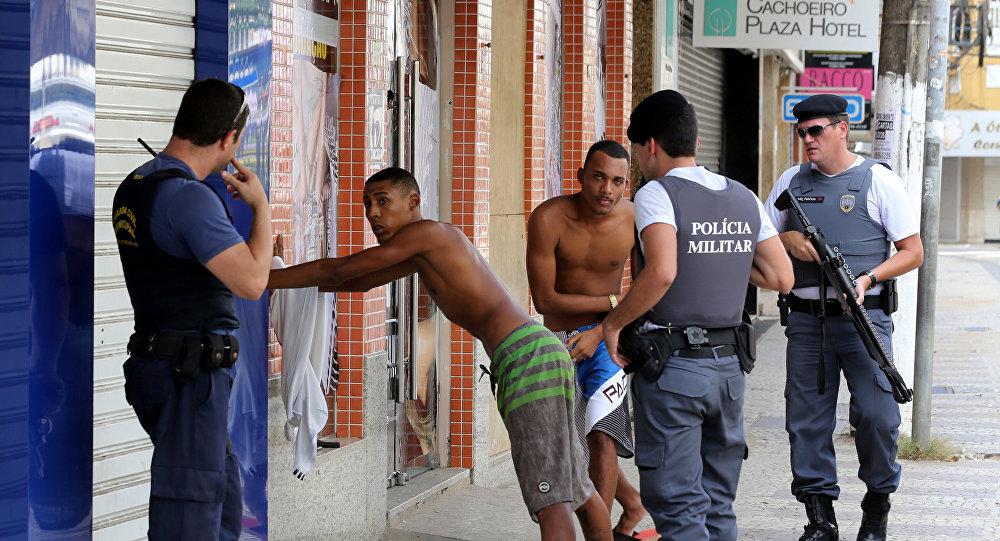 Agentes da PM examinam dois homens em Cachoeira do Itapemirim, ES, em 7 de fevereiro de 2017