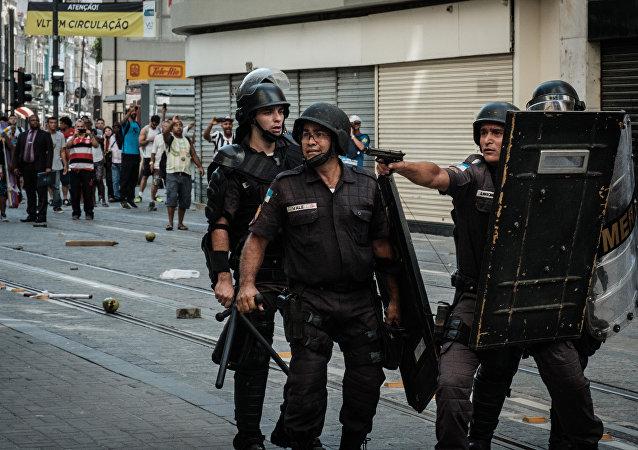 Policial aponta arma de fogo para manifestantes em protesto no Rio de Janeiro, 9 de fevereiro de 2017