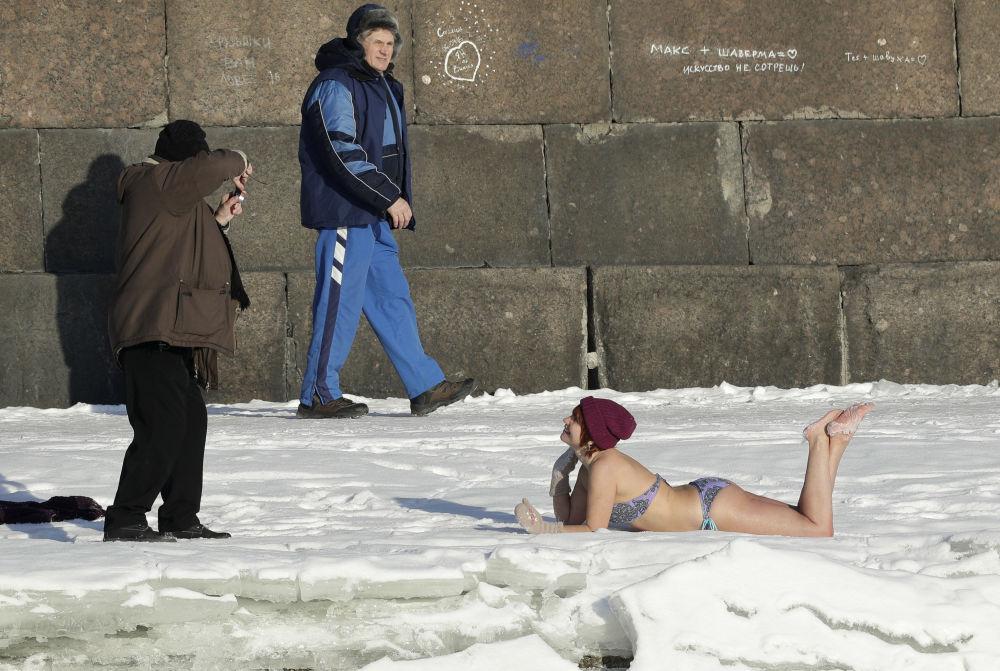 Moça toma banhos de sol em plena neve, com 12 graus negativos, perto da Fortaleza de São Pedro e São Paulo na cidade russa de São Petersburgo.