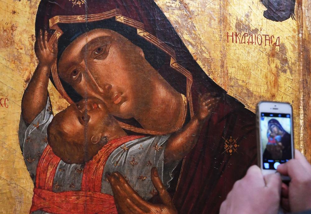 Visitante da Galeria Tretyakov tira foto do ícone A Virgem e o Menino na abertura da exposição Obras-primas do Império Bizantino.