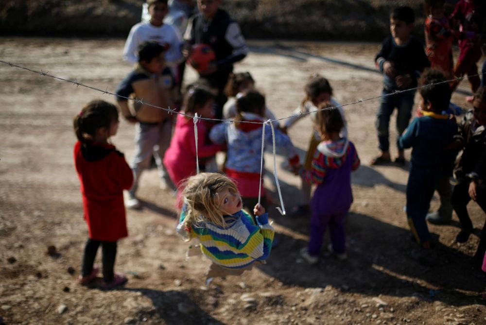 Crianças iraquianas deslocadas que fugiram do baluarte jihadista de Mossul com suas famílias brincam no campo de refugiados de Khazer.
