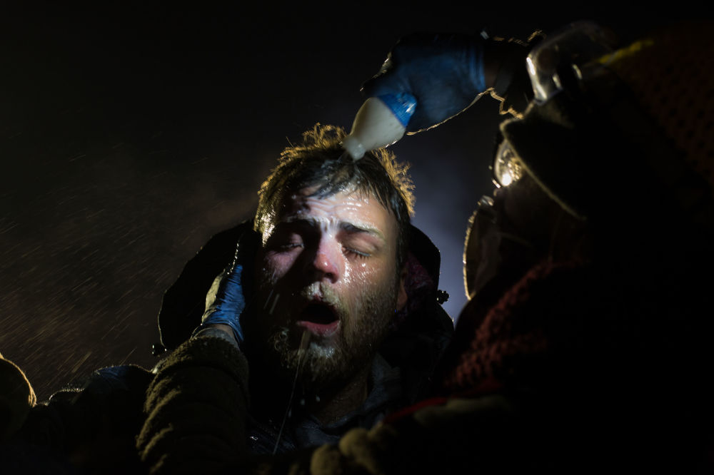 Imagem tirada por Amber Bracken retrata um homem sendo tratado com leite de magnésio pela polícia após ter sido atacado com gás de pimenta durante uma greve no estado de Dakota do Norte