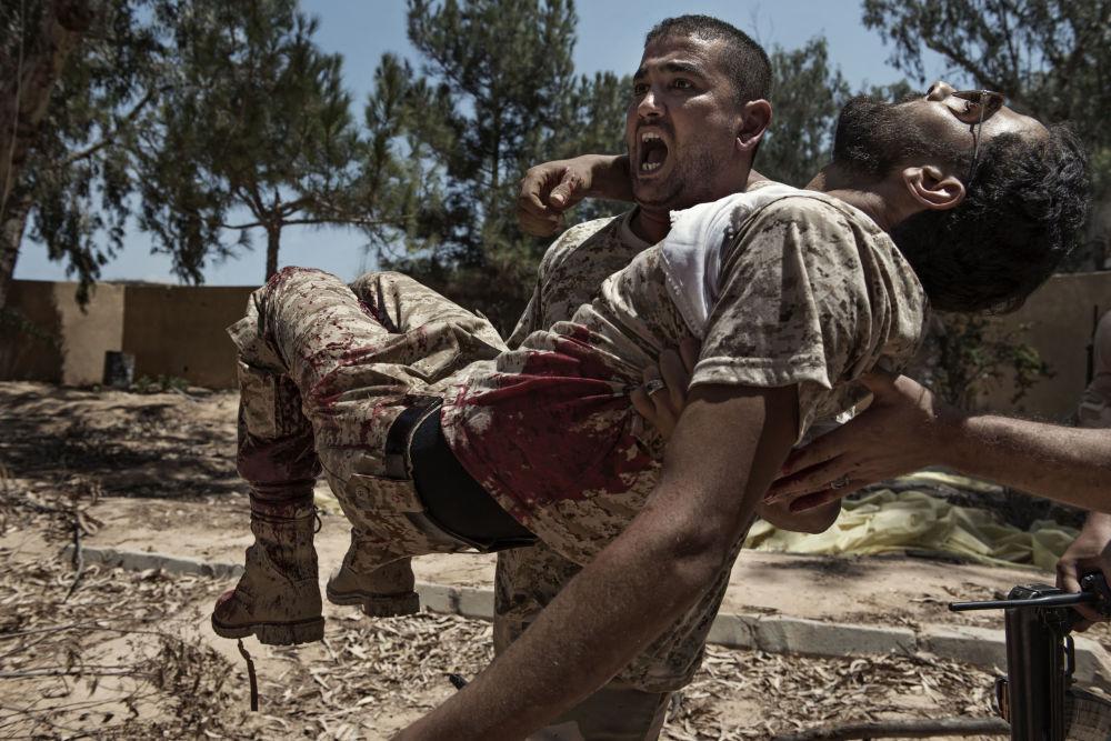 Foto de Alessio Romenzi mostra um combatente das forças líbias leais ao governo de Trípoli carregando seu camarada gravemente ferido por uma armadilha colocada pelos militantes do Daesh, na Líbia