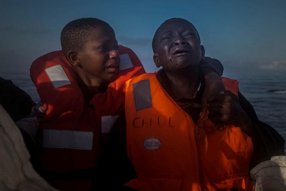 Foto Deixado Sozinho, tirada por Santi Palacios, retrata uma menina nigeriana de 11 anos (à esquerda), que falou sobre a morte de sua mãe na Líbia, sentada ao lado do seu irmão (à direita) dentro de um barco de resgate