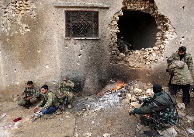 Os rebeldes descansam perto de um buraco na parede nos arredores da cidade sírio de al-Bab, na Síria 15 de janeiro de 2017