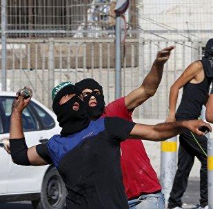 Palestinos lançam pedras contra a polícia de fronteira israelense durante confrontos em um posto de controle entre o campo de refugiados de Shuafat e Jerusalém, 18 de setembro de 2015
