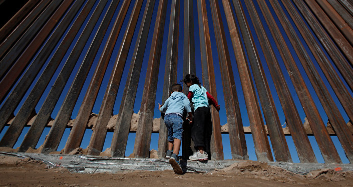 Children play at a newly built section of the U.S.-Mexico border wall at Sunland Park, U.S. opposite the Mexican border city of Ciudad Juarez, Mexico November 18, 2016