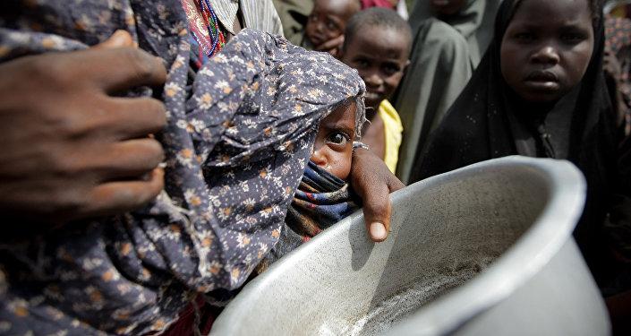 Uma mulher segurando um bebê espera por comida em um campo para desabrigados perto de Mogadíscio, Somália (Arquivo)