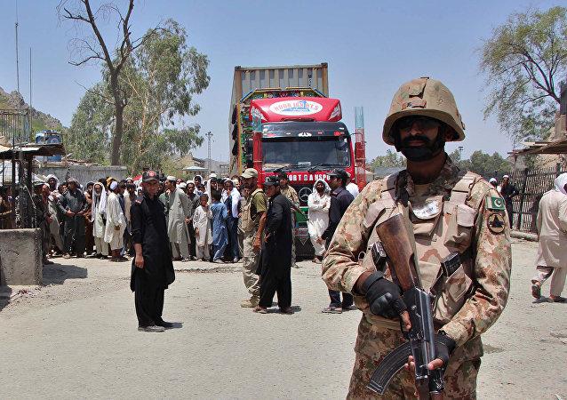 Soldado paquistanês em guarda enquanto caminhão entra no Paquistão vindo do Afeganistão, na passagem de fronteira de Torkham