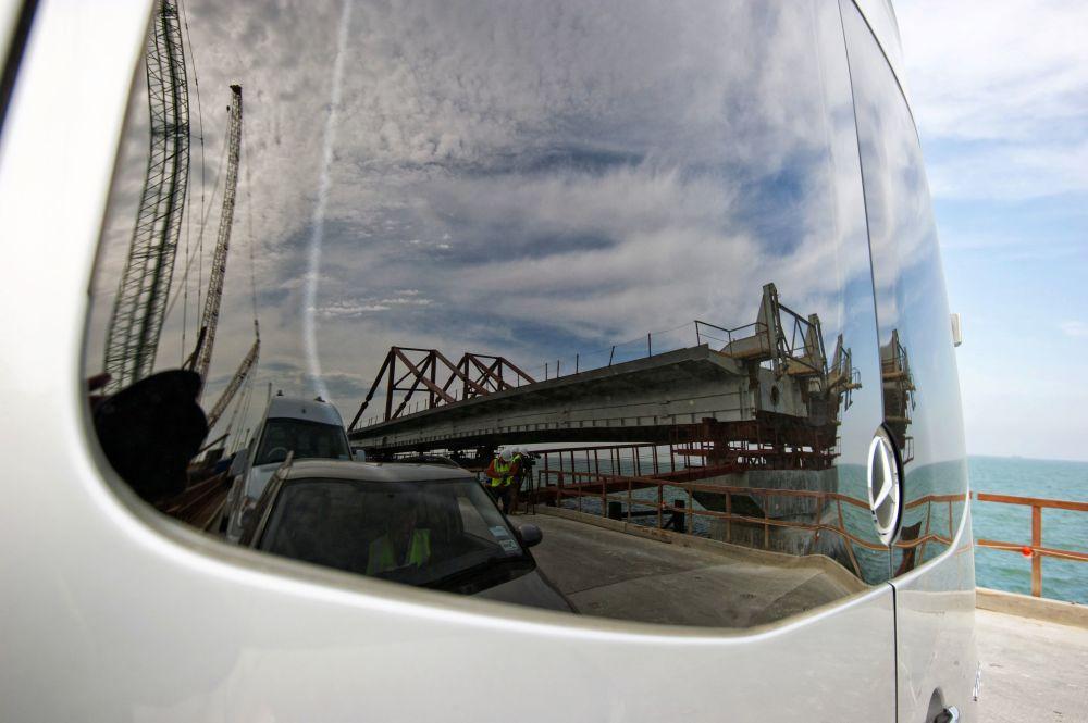 Construção da rodovia é refletida no vidro de um carro