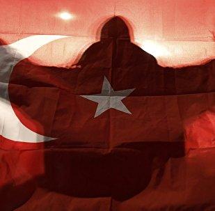 Manifestante com bandeira da Turquia em frente ao consulado turco em Roterdã