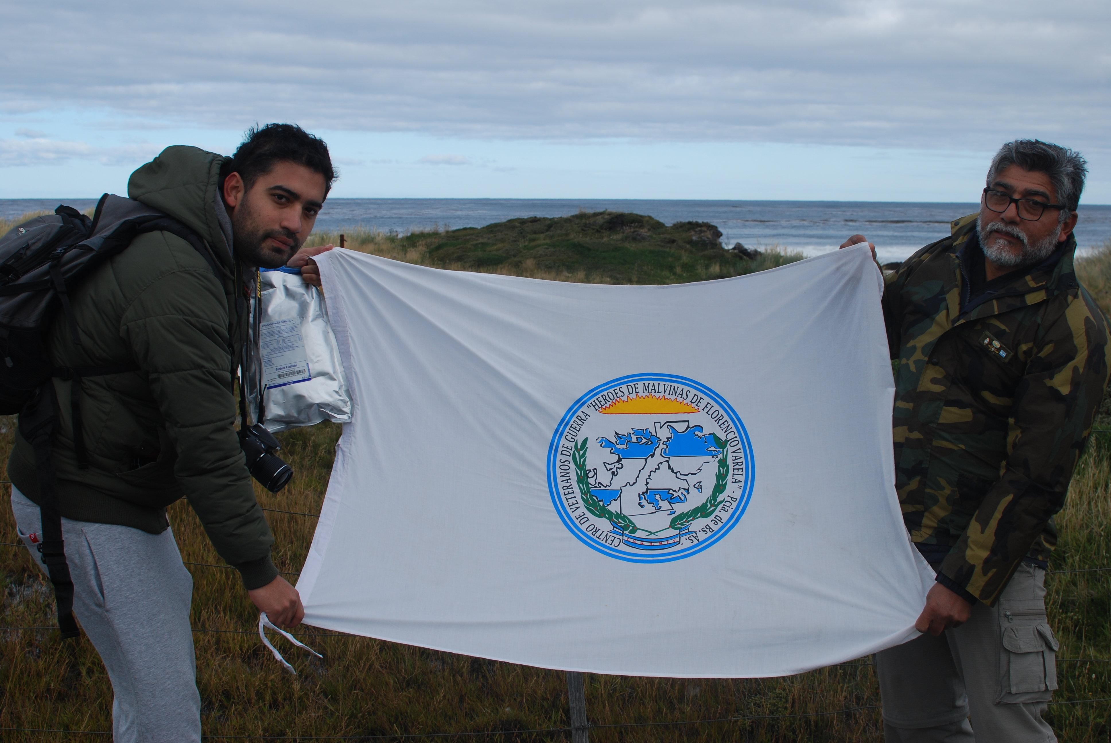 Ex-combatente da Guerra das Malvinas Armando González e seu filho Martín seguram a bandeira de um grupo de heróis do conflito na praia onde se defendeu o regimento