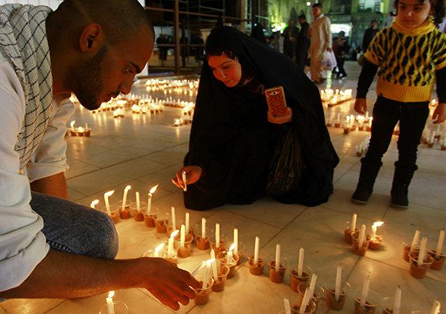 Iraquianos participam de uma vigília à luz de velas no santuário de Imam Ali, na cidade central do Iraque de Najaf, em 27 de fevereiro de 2015, em memória das vítimas muçulmanas e cristãs mortas pelo Estado Islâmico
