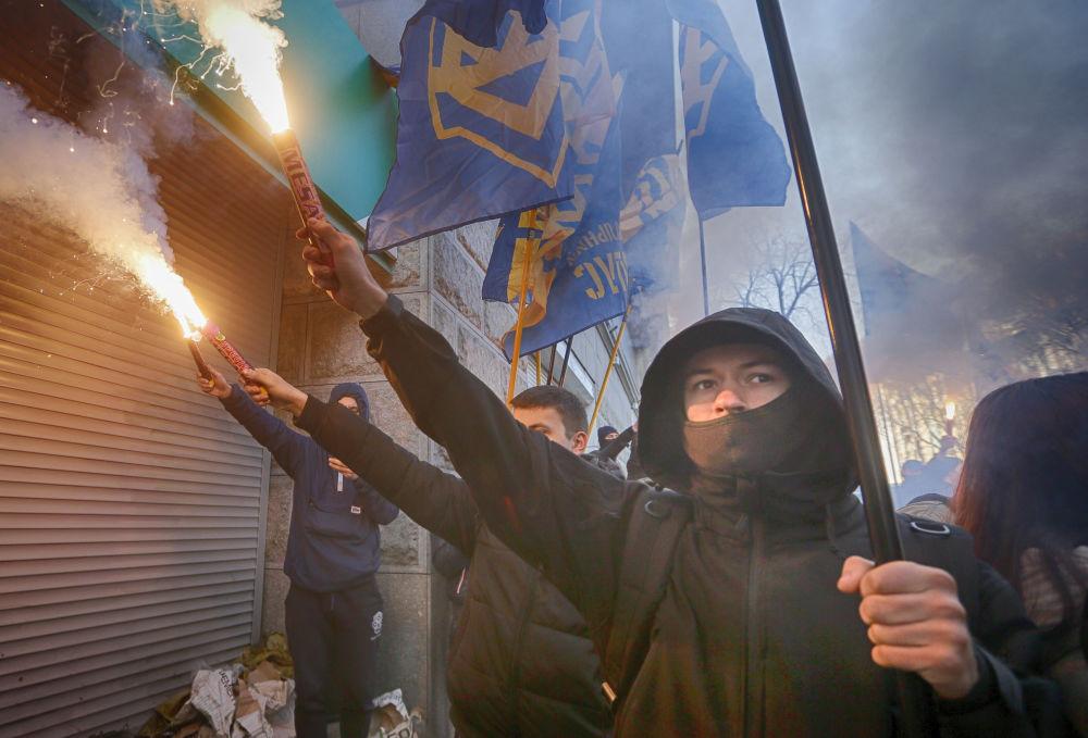 Membros do partido ucraniano Natsionalny Korpus (Corpo Nacional) na entrada da filial de um banco russo em Kiev