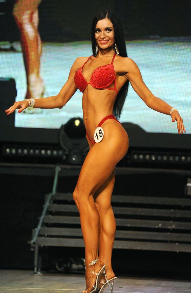 Uma participante com biquíni vermelho demonstra seu corpo musculoso durante o Campeonato aberto de fisiculturismo, fitness e desfile em biquíni na sala do Palácio da Cultura dos Trabalhadores Ferroviários em Chita, região de Transbaikal, Rússia