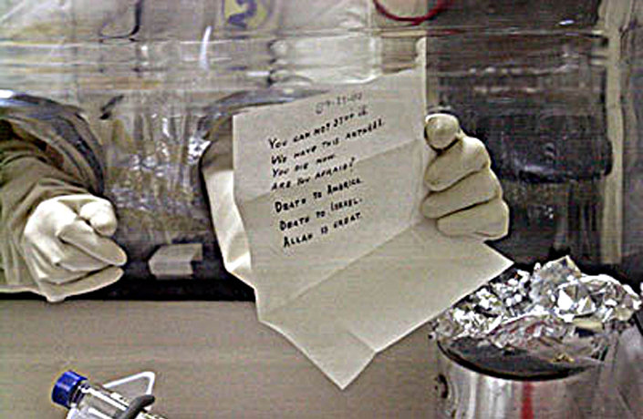 Esta foto de 5 de dezembro de 2001 mostra um especialista do laboratório de pesquisa biomédica de Fort Detrick, do Exército dos EUA, abrindo uma carta dirigida ao senador Patrick Leahy, de Vermont, achada na seção de correspondência recebida do Congresso em 16 de novembro de 2001
