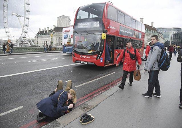 Uma mulher presta socorro a um ferido após incidente com tiroteio na ponte de Westminster em Londres, em 22 de março de 2017