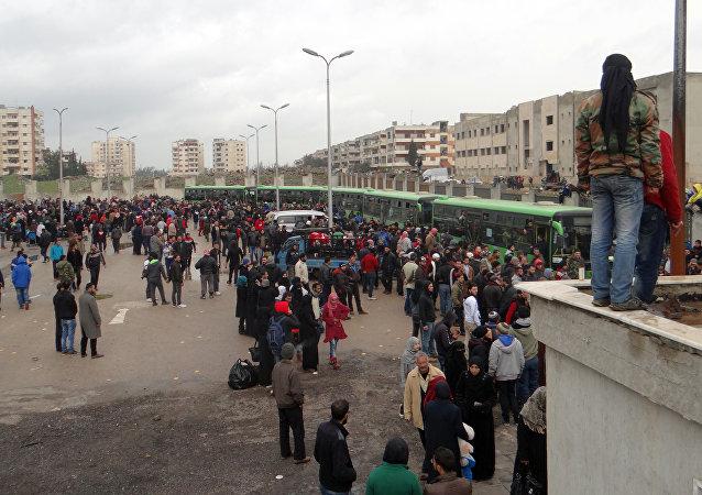 Combatentes da oposição e suas famílias se reúnem, enquanto se preparam para subir em um ônibus, antes da evacuação do bairro rebelde de Waer, na cidade de Homs, em 18 de março de 2017
