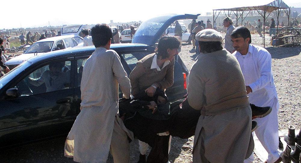 Homens paquistaneses levam um ferido na explosão no mercado em Parachinar, capital do distrito tribal de Kurram, em 13 de dezembro de 2015.