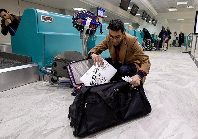 Viajante líbio acomoda o laptop na mala para despachar, antes do vôo para Londres, no Aeroporto Internacional de Túnis-Cartago, 25 de março de 2017