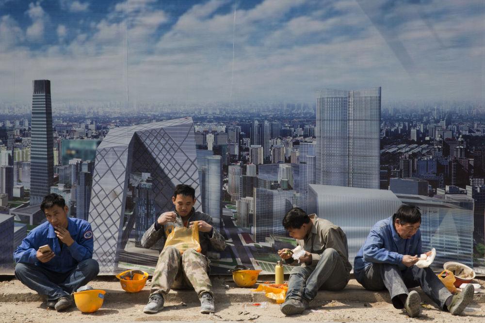 Trabalhadores descansam na hora de almoço em Pequim