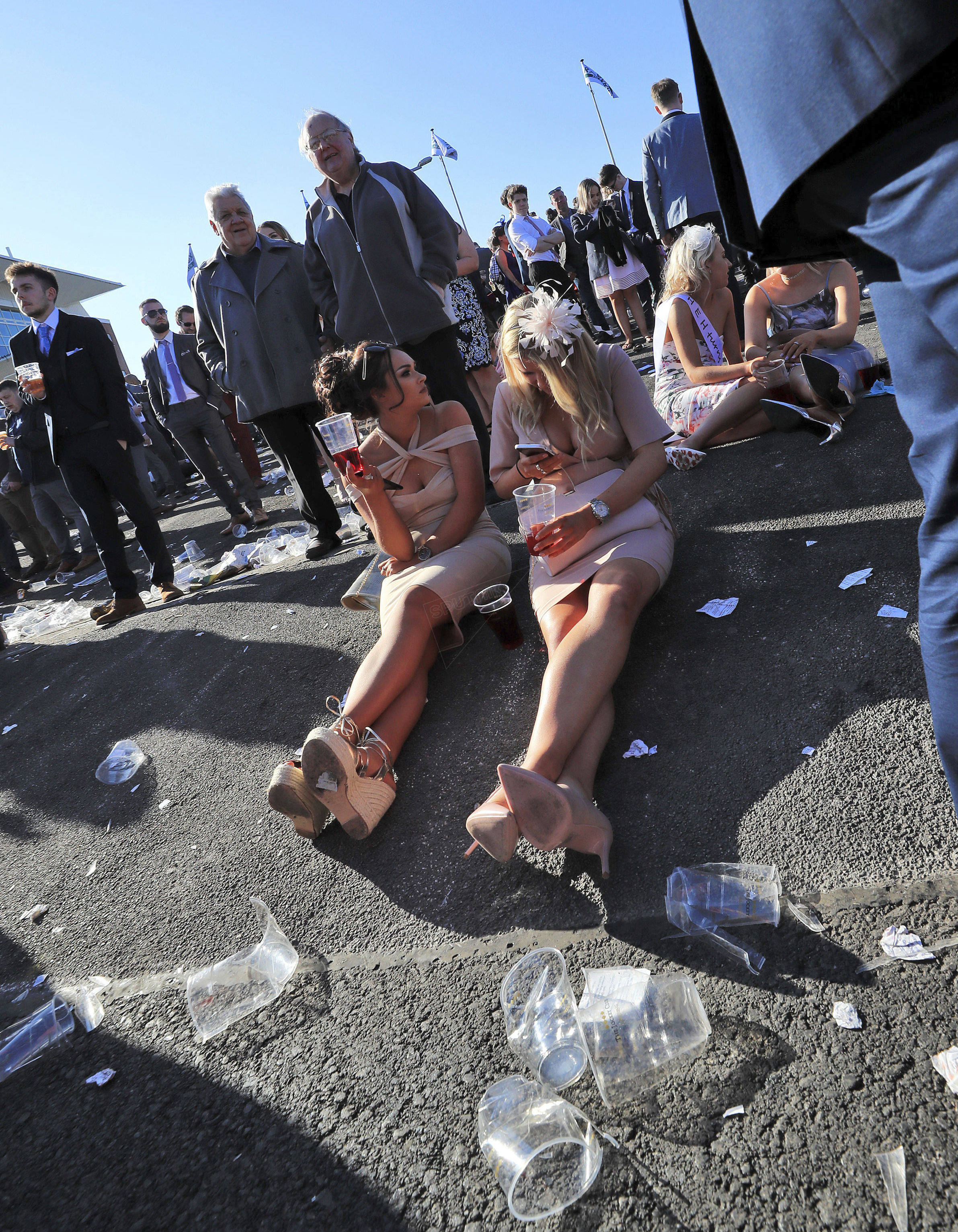 Duas britânicas estão sentadas no asfalto rodeadas por lixo