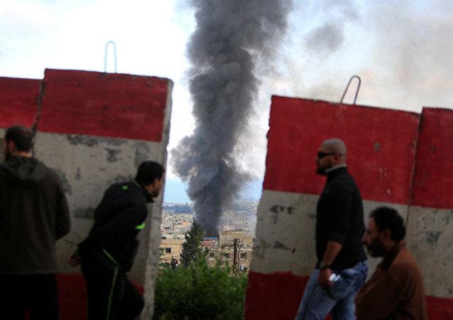 Refugiados atrás de uma barreira do Exército libanês enquanto a fumaça aumenta durante os confrontos entre os islâmicos e os atiradores palestinos da Fatah no campo de refugiados palestinos de Ain al-Hilweh perto de Sidon, no sul do Líbano 9 de abril de 2017