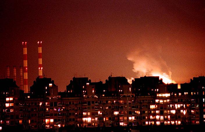 Chamas dos incêndios em resultado dos ataques aéreos da OTAN iluminam o céu de Belgrado, Iugoslávia, 24 de março de 1999