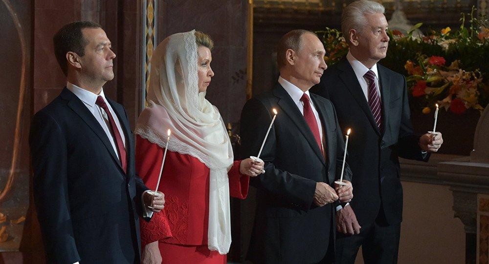 O presidente russo, Vladimir Putin, o premiê Dmitry Medvedev, com sua esposa Svetlana, e o prefeito de Moscou, Sergei Sobyanin, durante uma missa pascal em Moscou, em 16 de abril de 2017