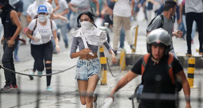 Manifestantes fogem da polícia durante os protestos contra o presidente venezuelano Nicolás Maduro em Caracas