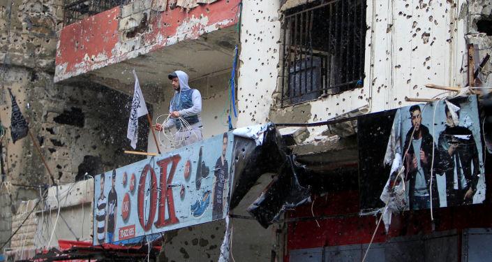 Homem na varanda de um dos edifícios com marcas de bombardeios em um campo de refugiados na Líbia (Arquivo)