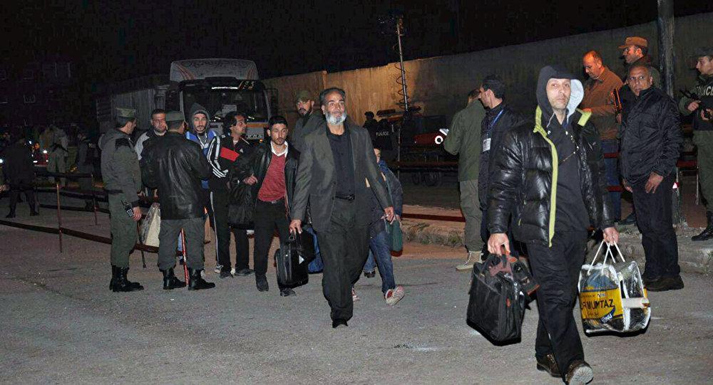Militantes, que lutam contra o governo sírio, rumo a um ônibus para deixar o bairro Al Waer, o último dominado por militantes na província de Homs, Síria.