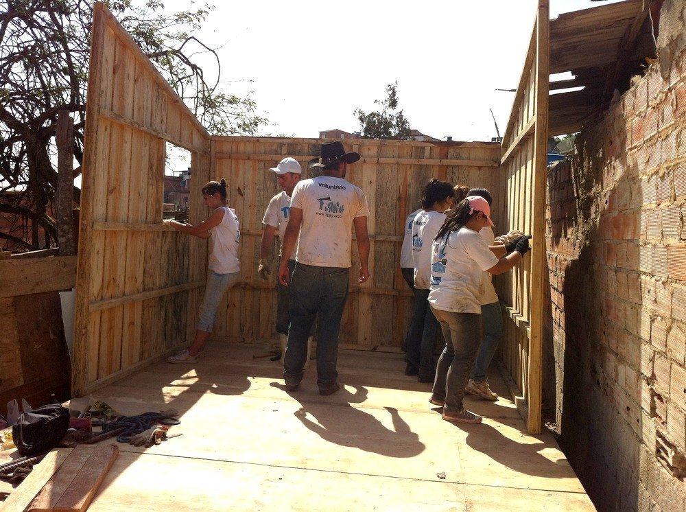 Voluntários da ONG Teto ajudam na construção de casas nas favelas