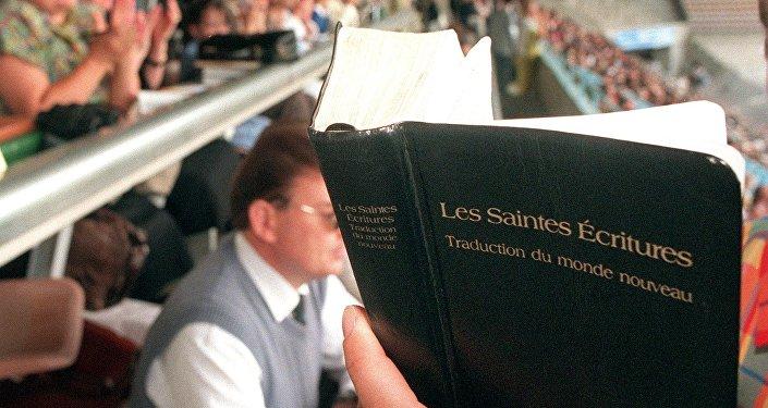 Testemunha de Jeová lê a Bíblia no estádio Meinau, em Estrasburgo, durante uma Assembleia regional que reuniu cerca de 12 mil Testemunhas de Jeová (1998 - foto de arquivo)