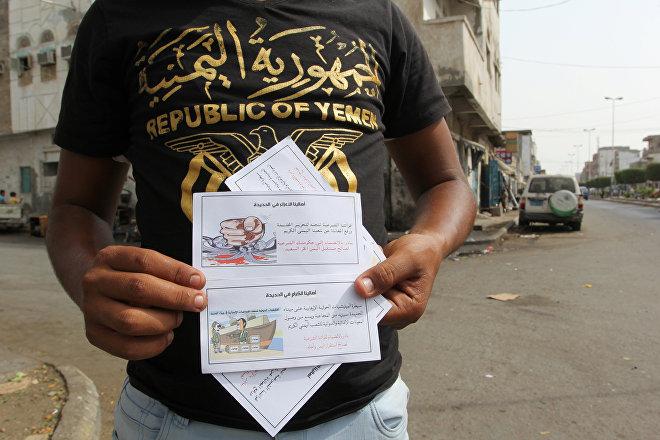 Um homem mostra folhetos deixados pela força aérea da coalizão saudita na cidade portuária de Hodeidah, no Iêmen, no Mar Vermelho. Os folhetos dizem: As nossas forças de legitimidade estão a caminho de libertar Hodeidah e acabar com o sofrimento de nosso amável povo iemenita. Junte-se a seu governo legítimo em favor do Iêmen livre e feliz!