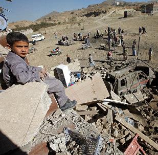 Um menino olha para a câmera enquanto se senta nos destroços de uma casa destruída por um ataque aéreo liderado pelos sauditas nos arredores de Sanaa, Iêmen.