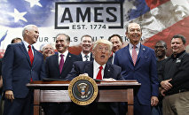 President Donald Trump, joined by Vice President Mike Pence, Secretary of Veterans Affairs David Shulkin, Secretary of Commerce Wilbur Ross, and others looks up as he signs an Executive Order on the Establishment of Office of Trade and Manufacturing Policy at The AMES Companies, Inc., in Harrisburg, Pa., Saturday, April, 29, 2017