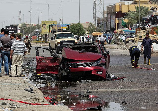 Civis e forças de segurança em volta de um carro que explodiu em Talibiya, no leste de Bagdá
