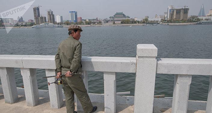 Morador de Pyongyang na marginal do rio Taedong