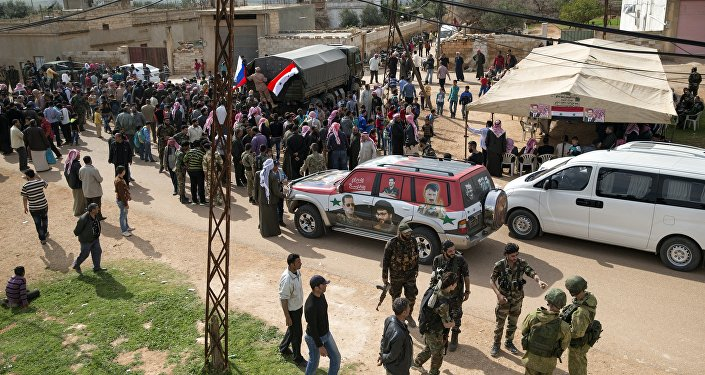 People gather around a Russian military truck to receive a food aid in Maarzaf, about 15 kilometers west of Hama, Syria, Wednesday, March 2, 2016