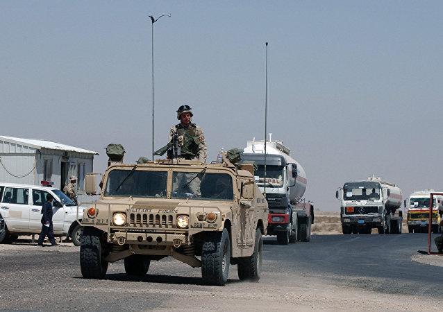 Um comboio de caminhões-tanques de combustível escoltados por um veículo do Exército dos EUA entra no Kuwait no posto fronteiriço militar de Abdaly na fronteira Kuwait-Iraque neste arquivo foto tirada em janeiro de 2006.