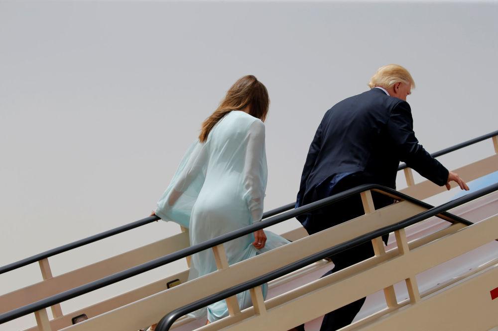 O presidente dos EUA Donald Trump, com sua esposa Melania, durante o embarque no seu avião
