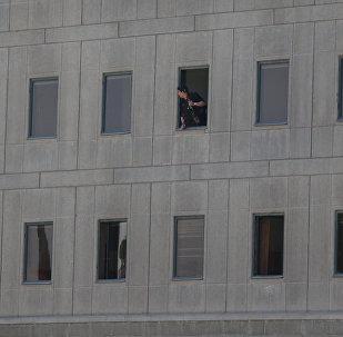 Policial iraniano olhando da janela do edifício do Parlamento iraniano