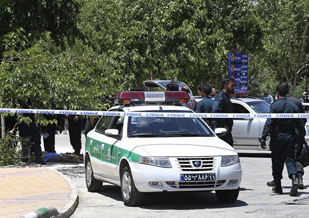 Corpo do suspeito terrorista deitado no chão e cercado por policiais perto do Mausoléu do aiatolá Khomeini, Irã, 7 de junho de 2017