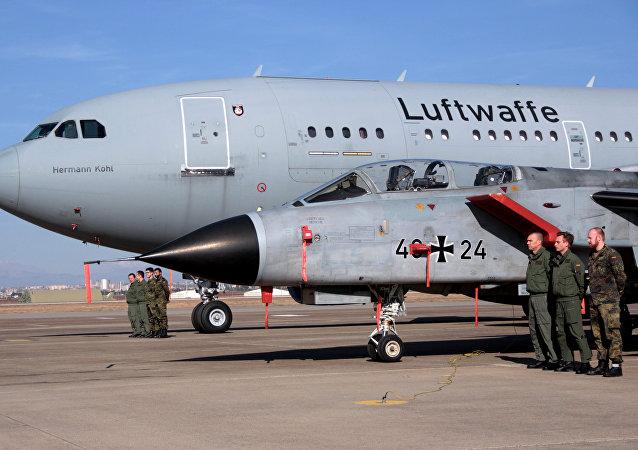 Um grupo de pilotos de guerra da Alemanha são vistos perto de um caça e de uma aeronave de transporte após a visita à base aérea turca de Incirlik do secretário de Defesa norte-americano, Ashton Carter, em 15 de dezembro de 2015