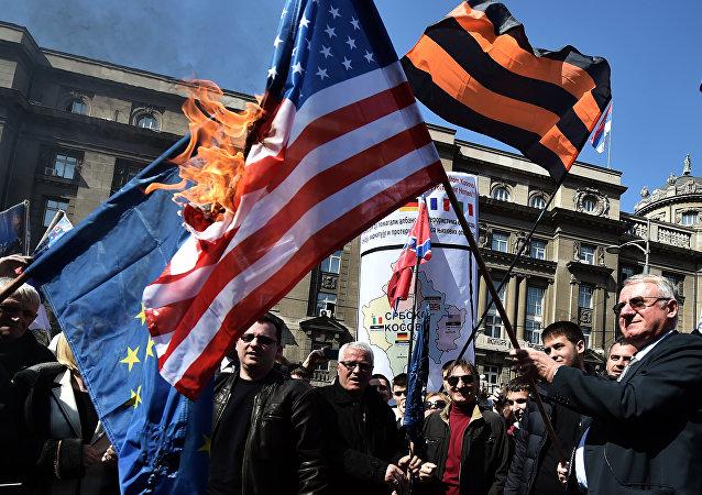 O político nacionalista sérvio Vojislav Seselj cercado por seus apoiadores mantém uma  bandeira da OTAN durante uma manifestação de oposição ao governo (foto de arquivo - 2015).