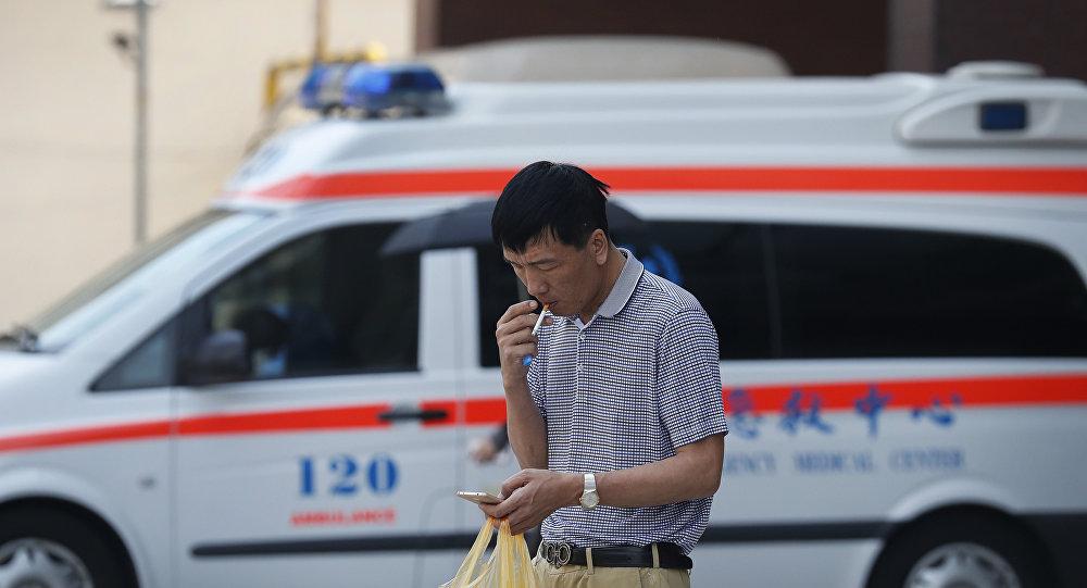 Um homem fuma um cigarro na frente de um carro de ambulância em Pequim em 31 de maio de 2017