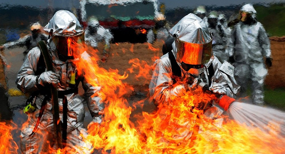 Uns bombeiros tentam apagar fogo (imagem referencial)