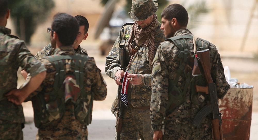 Um combatente norte-americano, que está lutando ao lado das Forças Democráticas da Síria, segura bandeira do seu país